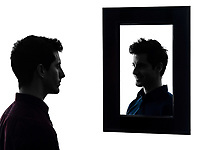 man in front of his mirror serious in shadow white background