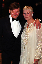 """Actress Dame Judi Dench, (who plays """"M""""), and her husband actor Michael Williams arrive at the European Charity Premiere of """"The World Is Not Enough"""", which stars Pierce Brosnan as James Bond, at the Odeon Leicester Square, London.  *  25/11/2000:  Actor Michael Williams has received a Papal knighthood for his contribution to Catholic life in Britain.  Williams, who played alongside his wife in TV's A Fine Romance, has been appointed a Knight of St Gregory, one of the highest honours conferred by the Catholic Church."""