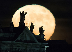 CAPTION CORRECTION © Licensed to London News Pictures. 14/12/2016. London, UK. The last Super Moon of 2016 rises above statues on St Paul's Cathedral. Photo credit: Peter Macdiarmid/LNP