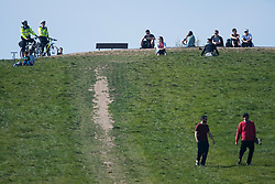 © Licensed to London News Pictures. 15/04/2020. London, UK. Police officers on bike watch over people sitting down on Primrose Hill, North London, during a pandemic outbreak of the Coronavirus COVID-19 disease. The public have been told they can only leave their homes when absolutely essential, in an attempt to fight the spread of coronavirus COVID-19 disease. Photo credit: Ben Cawthra/LNP
