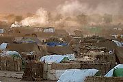 Smoke from cookfires wafts up into the sky at dawn in Breidjing Refugee Camp in eastern Chad. (From the book What I Eat: Around the World in 80 Diets.) The sunrise ushers in another day of waiting. It's November, two months after the rainy season, but  temperatures are still low. Women sweep the dirt in front of their tents while children walk to the water depot with empty plastic containers as roosters crow and donkeys bray into the desert air, which is beginning to lose its nighttime chill.
