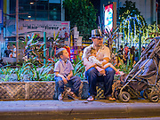 31 DECEMBER 2014 - BANGKOK, THAILAND: A man and his kids sit on the median of Phloen Chit Road near the New Year's party in Rathaprasong. Hundreds of thousands of people pack into the Ratchaprasong Intersection in Bangkok for the city's annual New Year's Eve countdown. Many Thais go the Erawan Shrine and Wat Pathum Wanaram near the intersection to pray and make merit before going to their New Year's parties.    PHOTO BY JACK KURTZ