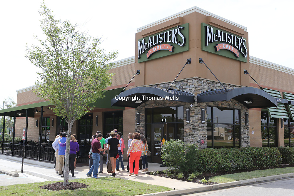 A small group gathers outside the new location of McAlister's Deli on South Gloster which opened on Thursday.