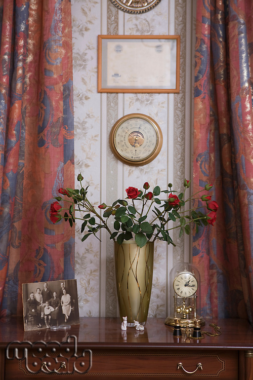 Roses in vase with carriage clock and faded family photograph