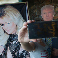 ORIG 05/17/18 A customer takes a picture of herself with a poster of Stormy Daniels and cutout of President Donald Trump while waiting to enter Stars Cabaret in Bend on Thursday, May 17, 2018.<br /> (Ryan Brennecke/Bulletin photo)