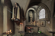 The Chapelle des Cierges or Chapelle St Louis, with statue of a nun and statue of St Louis, or Louis IX of France, 1214-70, with candles burning, in the Basilica of Liesse Notre Dame, built 1134 in Flamboyant Gothic style by the Chevaliers d'Eppes, then rebuilt in 1384 and enlarged in 1480 and again in the 19th century, Liesse-Notre-Dame, Laon, Picardy, France. Pilgrims flock here to worship the Black Virgin, based on Ismeria, the Soudanese daughter of the sultan of Cairo El-Afdhal, who saved the lives of French knights during the Crusades, converted to christianity and married Robert d'Eppes, son of Guillaume II of France. Picture by Manuel Cohen