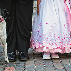 A man, woman, girl and dog standing on a cobblestone road, showing off their footwear.