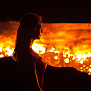 A woman is silhouetted against the burning gas of the Darvaza crater in the Karakum Desert, Turkmenistan