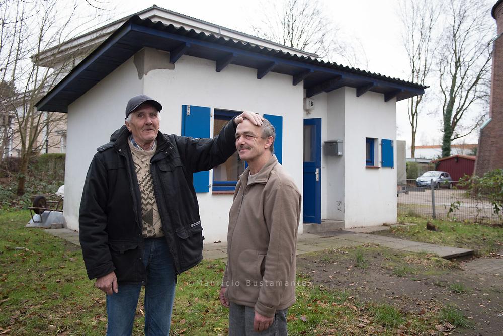 Hinter Dieter und Ralf sieht man eine KIRCHENKATE bei der Kirchengemeinde in<br /> Volksdorf mal von au&szlig;en. Hier kann eine Person auf 18 Quadratmeter leben, mit kleiner eigener<br /> Küche und Bad. Hier k&ouml;nnen sich die beiden von ihrer Zeit drau&szlig;en erholen und Kraft tanken.