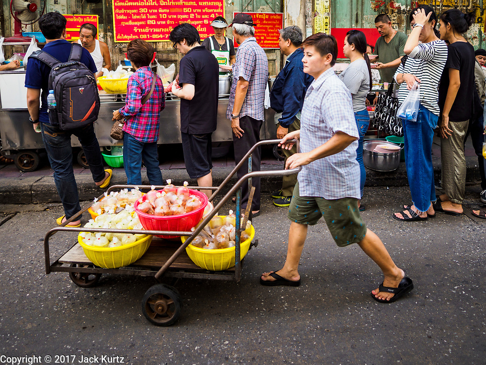"18 MAY 2017 - BANGKOK, THAILAND: A woman deivers curry to Jek Pui curry stand, a popular street food stall for curry dishes. The curry is prepared in a family kitchen about one block away. City officials in Bangkok have taken steps to rein in street food vendors. The steps were originally reported as a ""ban"" on street food, but after an uproar in local and international news outlets, city officials said street food vendors wouldn't be banned but would be regulated, undergo health inspections and be restricted to certain hours on major streets. On Yaowarat Road, in the heart of Bangkok's touristy Chinatown, the city has closed some traffic lanes to facilitate the vendors. But in other parts of the city, the vendors have been moved off of major streets and sidewalks.      PHOTO BY JACK KURTZ"