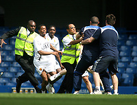 LONDON, ENGLAND - Saturday, April 26th, 2008:  Manchester United's Patrice Evra tries to attack a groundsman as the players warm down after the game against Chelsea during the Barclays Premiership match at Stamford Bridge. (Photo by Chris Ratcliffe/Propaganda)