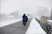 Nederland, Ubbergen, 13-1-2017De eerste sneeuw van deze winter is gevallen bij Nijmegen. Fietser en hardloper in een sneeuwbui.Foto: Flip Franssen