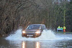 © Licensed to London News Pictures. 03/01/2014. Jacobs Well, UK .Men watch as cars pass through flood water created by the River Mole bursting it's banks at Jacobs Well in Surrey today 3rd January 2013. Floods an heavy rain are continuing to effect travel and people across the country today. Photo credit : Stephen Simpson/LNP
