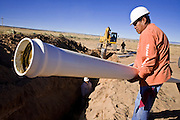 22 OCTOBER 2007 -- COYOTE CANYON, NM: CHUCK MORGAN, a member of a construction crew, installs water pipes on the Navajo Indian Reservation near Coyote Canyon. The project is a part of an effort by the tribe's government to bring potable water to the members of the Navajo Nation. More than 30 percent of the homes on the Navajo Nation, about the size of West Virginia and the largest Indian reservation in the US, don't have indoor plumbing or a regular supply of domestic water. Many of these homes have to either buy water from commercial vendors or haul water from public wells. A Federal study showed that the total cost of hauling water was about $113 per 1,000 gallons. A Phoenix household, in comparison, pays just $5 a month for up to 7,400 gallons of water. The lack of water on the reservation means the Navajo are among the most miserly users of water in the United States. Families that have to buy or haul water use only about 15 gallons of water per day per person. In Phoenix, by comparison, the average water use is about 170 gallons per day.  Photo by Jack Kurtz