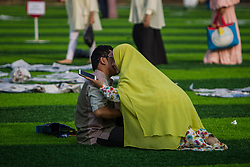 June 15, 2018 - Central Jakarta, Jakarta, Indonesia - Women kiss her husband after Eid Al-Fitr prayer on plastic grass at futsal stadium on June 15, 2018 in Jakarta, Indonesia. Muslims around the world are celebrating Eid al-Fitr, the three day festival marking the end of the Muslim holy month of Ramadan, it will be observed on 15th or 16th of June depending on the lunar calendar. Eid al-Fitr is one of the two major holidays in Islam. (Credit Image: © Afriadi Hikmal via ZUMA Wire)