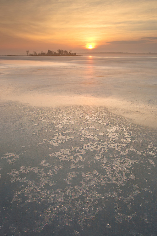 Hazy conditions and sunrise combine to spectacular winter morning light on  the frozen St. Lawrence River, Thousand Islands, Ontario, Canada