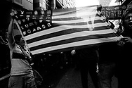 Demontrators showing altered American flag symbolizing corporate greed during the protest, San Francisco, 2003