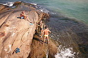 GROUP OF MEN SWIMMING OFF ROCKS RIO BRAZIL