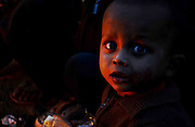 Unidentified Rohigya Muslim child is warming himself in front of a fire in her makeshift camp at the outskirts of Delhi State of India. <br /> More than 10,000-numbers of Burmese Rohingya Muslim refugee took shelter in Indian (Hyderabad) Andhra Pradesh, (Mewat) Haryana, (Kanchankunj) Delhi and Jammu States after ethnic strife between Rohingya Muslims and Buddhists that had been started since 1940s. Still so many peoples of aforesaid community have been living at various refugee camps in Myanmar, Bangladesh and India chiefly. Rohingya Muslims of Buthidaung, Rathedaung and Sittwe of Rakhine (formerly, Arakan) State, who ran away from Myanmar (that is, Burma) to Bangladesh to India and others South-Asian countries to escape socio-political-religious violence. (Photo/Shib Shankar Chatterjee)