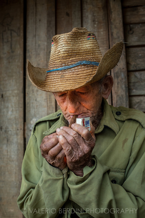 A farmer lights up a freshly handmade cigar. The face is lit by the flame of a match. Vinales valley, Cuba.