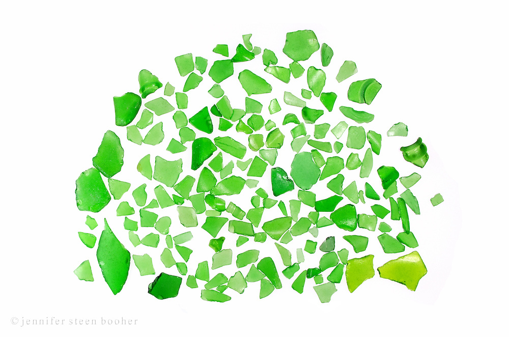 A pile of glowing green pieces of seaglass shimmer on the light table.