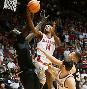 Alabama guard Collin Sexton (2) goes to the basket against seven foot six inch tall Central Florida center Tacko Fall (24) in Coleman Coliseum Sunday, Dec., 3, 2017.  [Staff Photo/Gary Cosby Jr.]