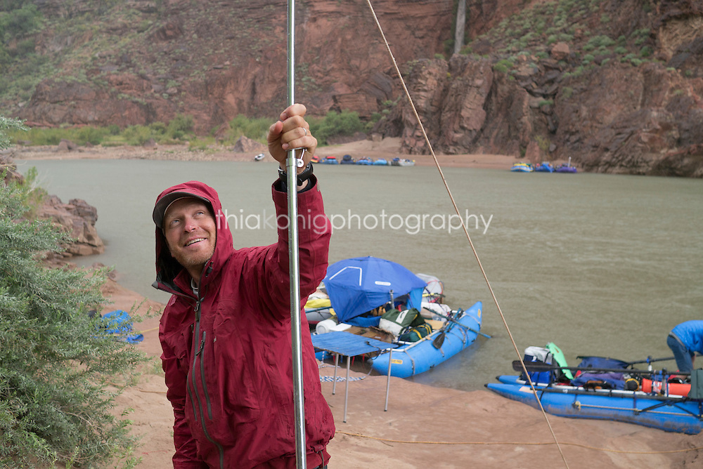 Man in red rain coat hold up tarp in rain storm, Deer Creek, Grand Canyon, AZ