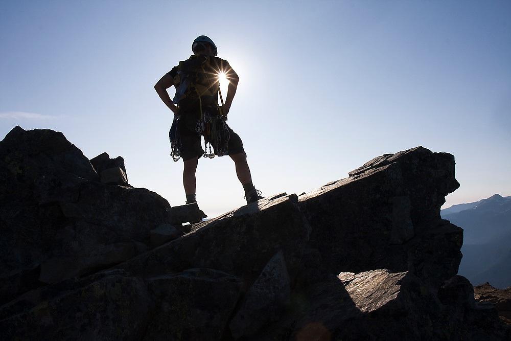 Climber Ian Derrington stands on the summit block of Pinnacle Peak during a traverse of the Tatoosh Range in Mount Rainier National Park, Washington.