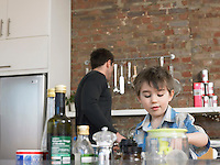 Father and son (3-4) in kitchen