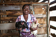 Linna Kinabo pictured with two of her chickens. <br /> <br /> Linna set up and now runs a poultry business selling both eggs and meat.<br /> <br /> She attended MKUBWA enterprise training run by the Tanzania Gatsby Trust in partnership with The Cherie Blair Foundation for Women.