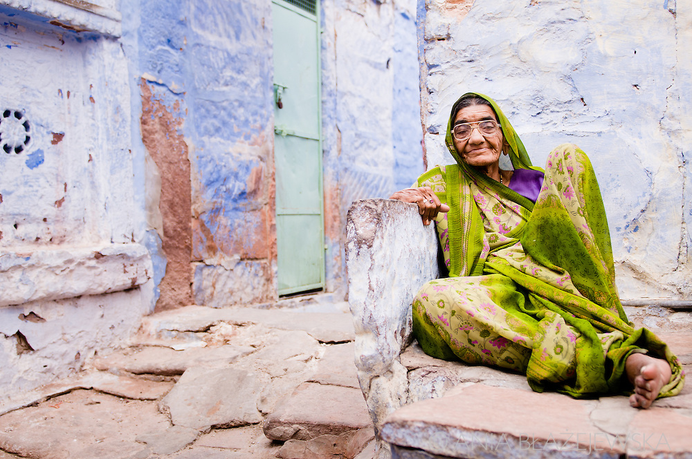 India, Jodhpur. Elderly Rajasthani woman wearing green sari rests near her blue painted house.