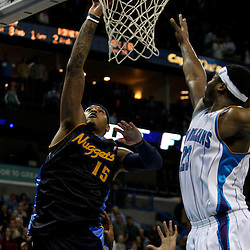 Dec 18, 2009; New Orleans, LA, USA;  Denver Nuggets forward Carmelo Anthony (15) shoots over New Orleans Hornets guard Devin Brown (23) during the second half at the New Orleans Arena. The Hornets defeated the Nuggets 98-92. Mandatory Credit: Derick E. Hingle-US PRESSWIRE
