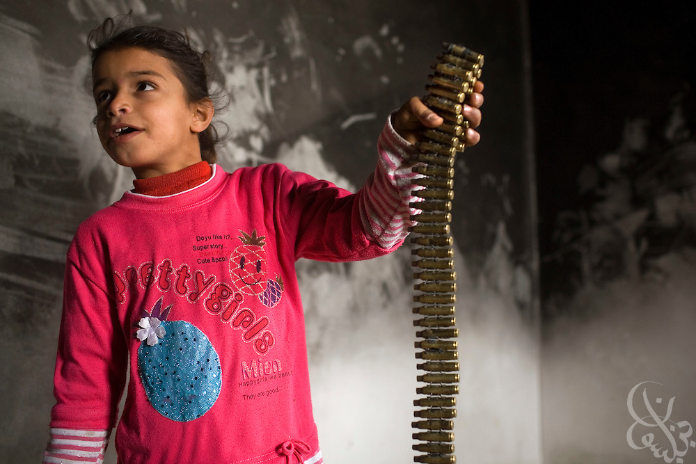 A Palestinian girl holds a belt of spent Israeli army ammo shell casings found in her house which was apparently used by Israeli Defense Forces during the recent 22 day operation inside Gaza January 24, 2009 in the village of Juhor al-Dik. From the graffiti left behind on the walls of Palestinian homes, along with food wrappers, Israeli newspapers, spent casings and sandbag sniper positions, it is apparent that Israeli infantry units occupied the homes of many Palestinians  during the operation.