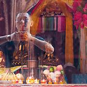 Man performing a prayer at the Lama Temple, Beijing, China