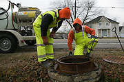 Jared Vobornik and Alex Faucher of Pipe-Eye Sewer clean a manhole in Lockport, New York on Friday, December 4, 2015. Pipe-Eye is based in Bradford, Pennsylvania.
