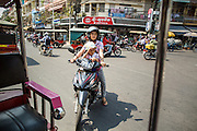 30 JANUARY 2013 - PHNOM PENH, CAMBODIA:  A man and his daughter navigate through traffic in Phnom Penh, Cambodia. Motorcycles are used as family transportation in most of Southeast Asia.    PHOTO BY JACK KURTZ