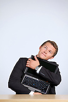 Businessman embracing laptop, looking up