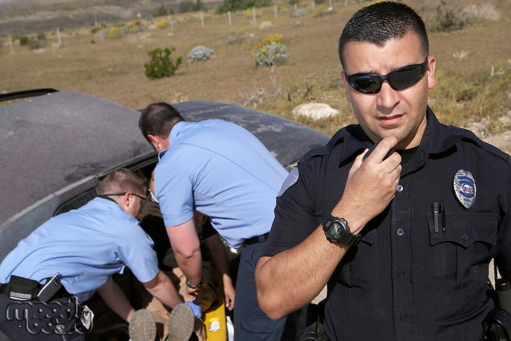 Portrait of police officer, paramedics rescuing car accident victim in background