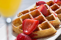 Food Photography detail shot of waffles and strawberries with a nearby mimosa. We built a temporary set outdoors right next to the beach in St. Petersburg, using reflectors to fill in the deep shadows in the waffle's indentations.