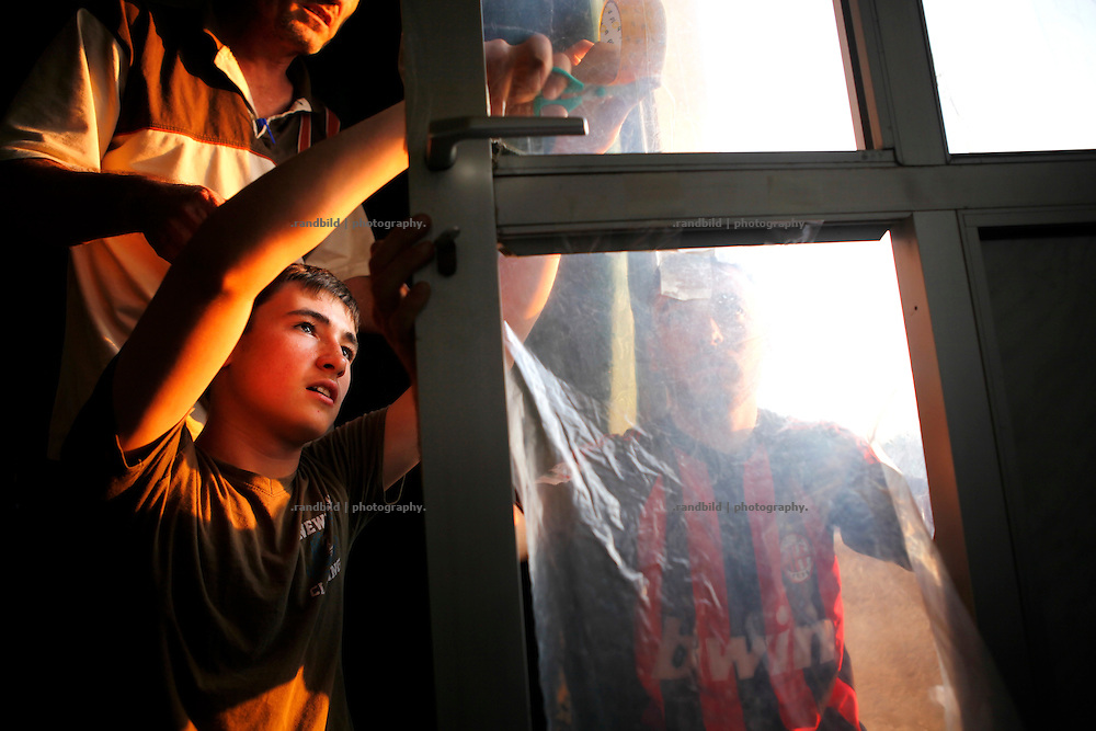 The two brothers Ahmad and Wissam taping plastic sheets into window and door frames in their families home. Almost all of the windows bursted off when Koreen was shelled by the regime forces.<br /> _ _ _ <br /> Idlib Interim - Challenging life without central government in the village of Koreen (Idlib Province, Syria)<br /> Koreen joint the syrian uprisung to ouster president Bashar al-Assad at a very early stage in 2011. It has been scene of Army attacks and heavy shelling since 2012. In the course of the fightings the village of a few thousend inhabitants was almost abandoned as barrel bomb campaings commited by the regime pounded Koreen. But since regime forces retreated to few bases remaining in Idlib province people returned home to establish a new and almost unregulated economic, social and community life. The regimes power has no affect and can&acute;t reach them anymore. On the other hand a new government isn&acute;t established yet and not in sight at all. Koreen is free to make its way.