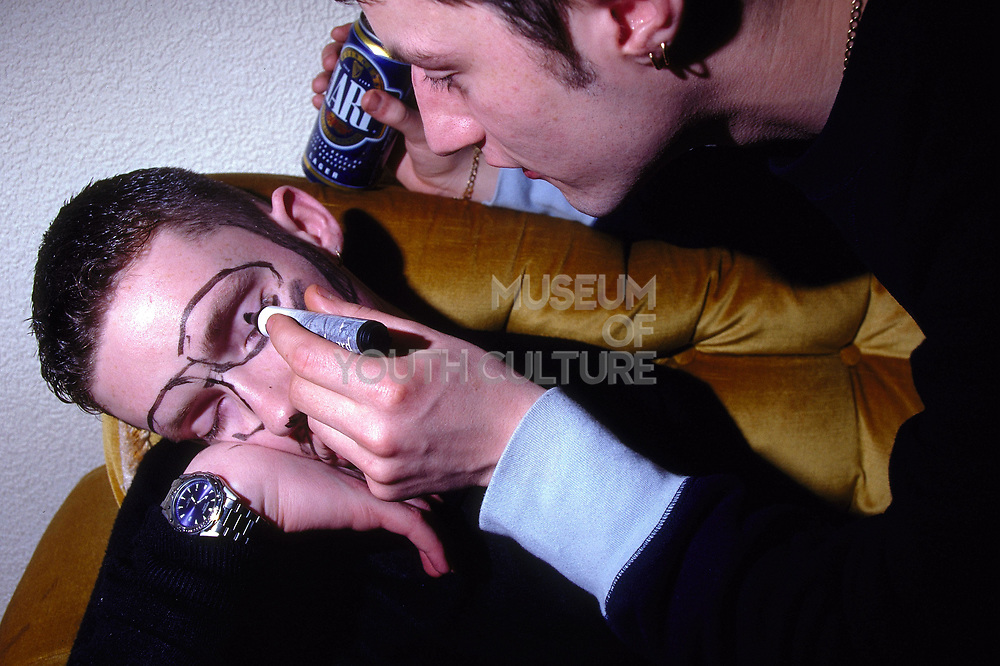 Young man drawing on his drunked sleeping friend's face with marker pen Inertia Derry Northern Ireland March 2002