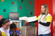 C&A volunteer reading to children at their community library, Biblioteca Chocolatao, Porte Alegre.