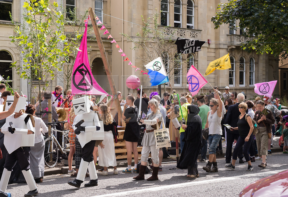 """© Licensed to London News Pictures. 30/08/2019. Bristol, UK. Extinction Rebellion Rebel Youth Alliance, The Film Industry Strikes Back event. Campaigners dressed as characters from Star Wars and the Bristol Fantasy Orchestra stage an event outside BBC Bristol Studios and the Natural History Unit calling on the film, television and theatre industries to join their cause. Extinction Rebellion have formed an alliance with the Youth Strike for Climate and are asking the film industry for help after hearing Greta Thunberg's call """"We need everyone"""" for a general strike, the Global Climate Strike on 20 September. The Rebel Youth Alliance hopes the film, television and theatre industries and its trade unions BECTU and Equity will join them and together use the industry's position as a cultural leader to press for change to avoid the collapse of civilisation and the deaths of millions. Photo credit: Simon Chapman/LNP."""