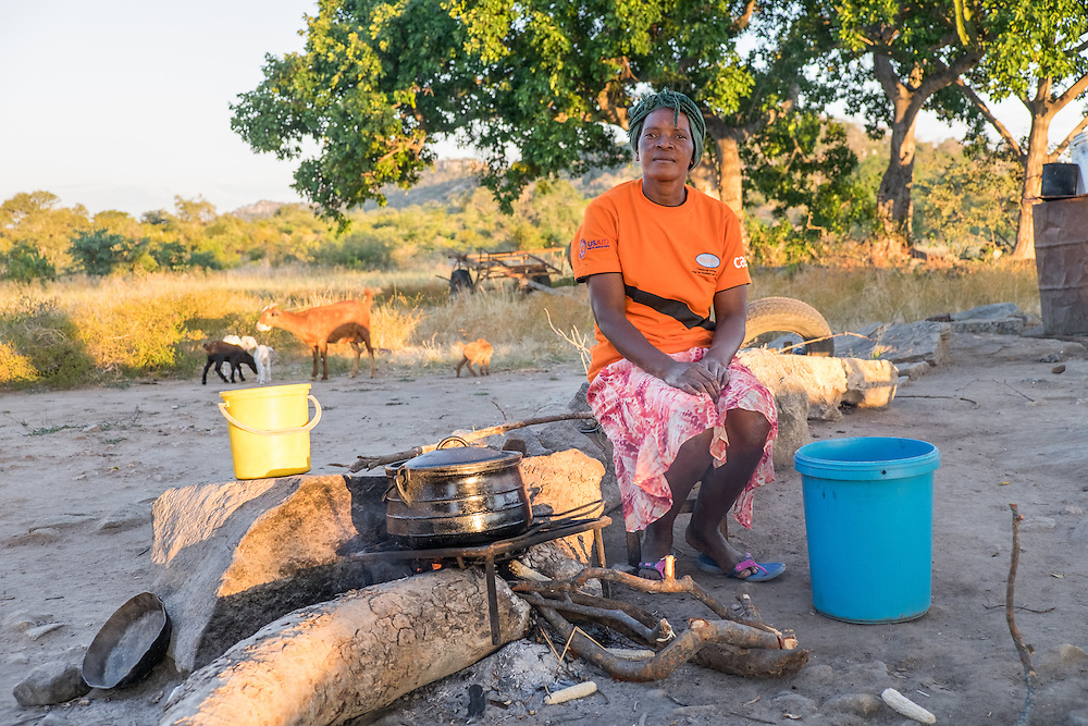 CAPTION: Sitting outside her home, Cathrine prepares an evening meal of sad (corn porridge) for her family, while her goats graze in the background. Sad is the staple food of the region, but the maize crop has been severely affected by recent droughts. Cathrine looks forward to the completion of the irrigation scheme, trusting that hunger will no longer affect the village once it's operating. She also hopes that more villagers will be able to afford to keep livestock, like she does. LOCATION: Mawoneke Village, Chivi District, Masvingo Province, Zimbabwe. INDIVIDUAL(S) PHOTOGRAPHED: Cathrine Mutero.