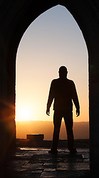 © Licensed to London News Pictures. 20/05/2015. Glastonbury, UK. A man standing in St. Michael's Tower watching the sunrise on Glastonbury Tor this morning, 20th May 2015. The day has started off clear, with early morning temperatures near freezing in places in the south west of England. Photo credit : Rob Arnold/LNP
