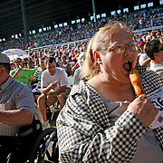 "Deborah Thornton, from Des Moines, Iowa, prepares to eat a corn dog, along with 8,500 other people, at the Iowa State Fair on August 7th.  As a promotional gimmick, an ""Iowa Corn Dog Chomp"" was held to set a world record for corn dog consumption at one place.  The fairgoers, in addition to getting a free corn dog, all got free admission to the fair that day."
