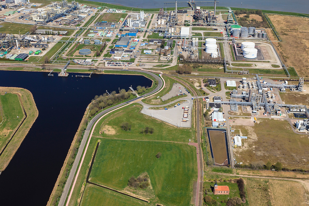 Nederland, Groningen, Delfzijl, 01-05-2013; Industrieterrein Eemsmondgebied met Chemie park. Het kerkje met dak van rode pannen is dat van het verdwenen dorpje Heveskes dat in het verleden ruimte moet maken voor het industrieterrein. Chemiepark.nl  huisvest onder andere AkzoNobel (soda, chloor, zout).<br /> Industrial Estate of the Eemsmond area with aluminum smelter Aldel (aluminum Delfzijl) right, to the left part of the Chemical Park. The little church with red roof tiles belongs to the village Heveskes, the village had to make room for the for the industrial park in the past Chemiepark.nl houses  Akzo Nobel (soda, chlorine, salt)<br /> luchtfoto (toeslag op standard tarieven);<br /> aerial photo (additional fee required);<br /> copyright foto/photo Siebe Swart