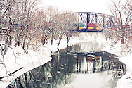An eastbound train of double-stacked ocean containers flies over the Spoon River at Dahinda, IL.