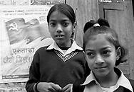 Two schoolgirls stand next a Maoist poster.