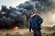 A police officer stands in front of a burning oil well in Qayyarah, set ablaze by retreating IS militants.